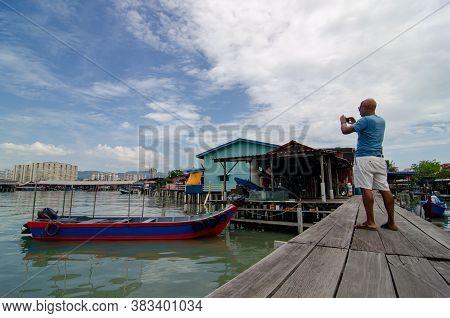 Georgetown, Penang/malaysia - Jun 02 2018: A Tourist Capture Photo At Clan Jetty.