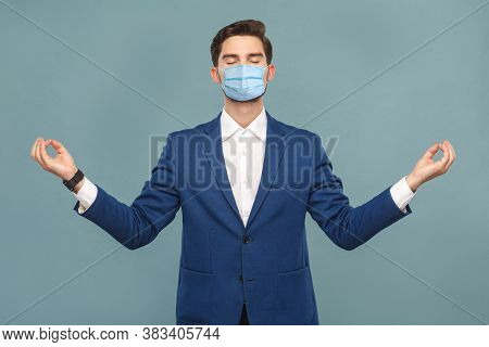 Yoga And Meditation. Young Calm Man With Surgical Medical Mask Standing And Relaxing.