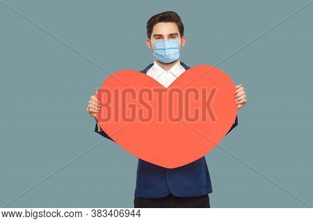 Happy Young Man With Surgical Medical Mask Standing, Holding Red Big Heart Shape.