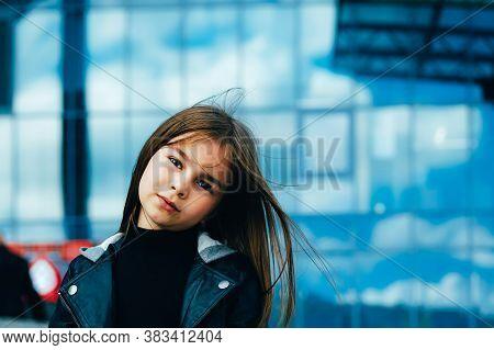 Little Urban Stylish Girl In Casual Autumn Clothes Walking Along Blue Glass Walls In Urban Surroundi