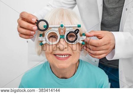 Smiling Senior Woman Wearing Optometrist Trial Frame At Ophthalmology Clinic. Ophthalmologist Helpin