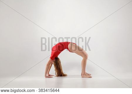 Young Woman In Red Leotard Balancing On Hands And Knees And Holding Back In Form Of Arch While Doing