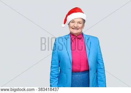 Satisfied Toothy Smiling Colorful Casual Style Aged Woman With Blue Suit And Christmas Santa Red Cap