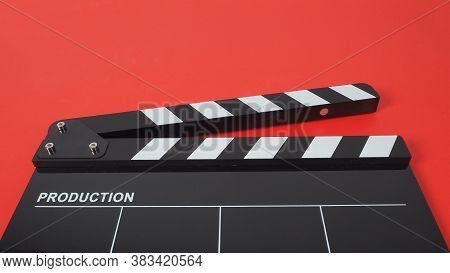 Black Clapperboard Or Movie Slate On Red Background.it Is Used In Video Production And Film Industry