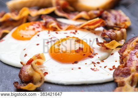 Sunny side up fried eggs with bacon on a plate