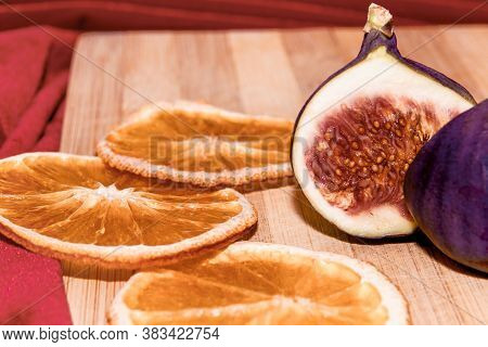 Figs Close Up. Pear-shaped Fruit. In The Foreground Are Dried Orange Slices In Blurred Focus And A S