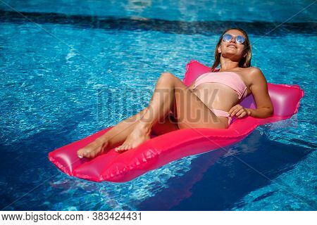 Sexy Female Model Resting And Sunbathing On A Mattress In The Pool. Woman In A Pink Bikini Swimsuit