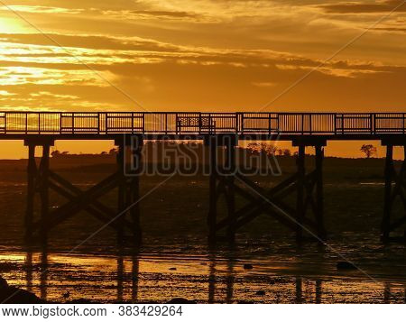 Fishing pier silhouette with sunris yellow colored sky and reflections in water