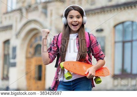 Active Ride. Happy Girl Skater Flex Arm Holding Penny Board Outdoors. Action Sport. Recreational Act