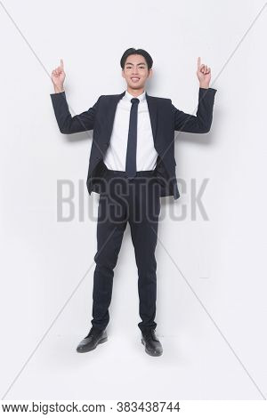 Men's beauty, fashion. Handsome full body young businessman wearing black suit and black pants , tie,black shoes with finger pointing up.
