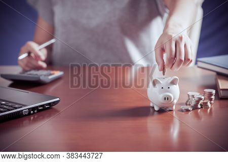 Female Hand Putting Money Into Piggy Bank With Using Calculator To Calculate And Money Stack, For Sa