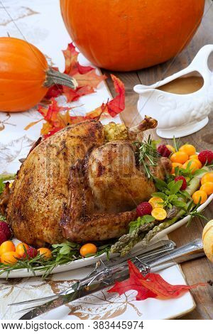Citrus Glazed Roasted Turkey For Thanksgiving Celebration Garnished With Kumquat, Raspberry, Asparag