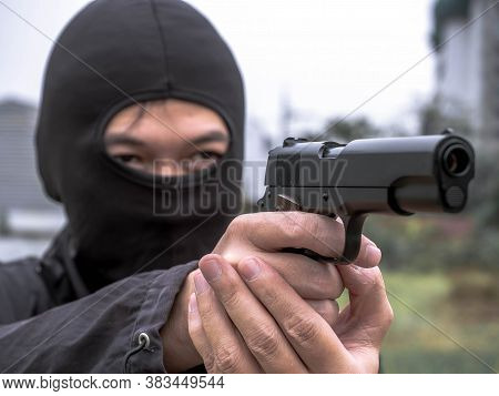 Man With The Gun In Dark Clothes, Robber In Black Hood Holding Gun And Pointing To Victim, Robbery C