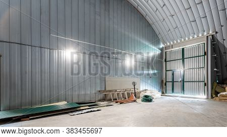 The Interior Of A Huge Industrial Warehouse Made Of White Bricks With A High Ceiling For Storing Goo