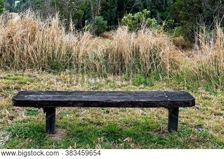 An Old Timber Bench Standing Alone And Forgotten In A Field Of Grass Amongst A Bushland Environment