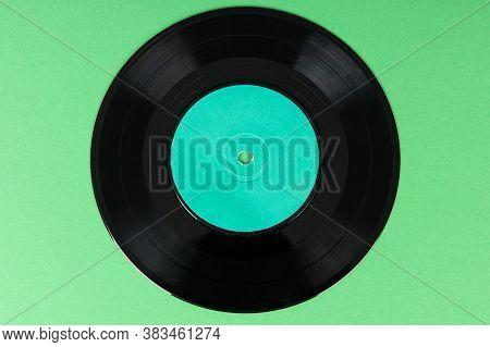 Old Vinyl Disc On Green Background. Old Vintage Vinyl Record.