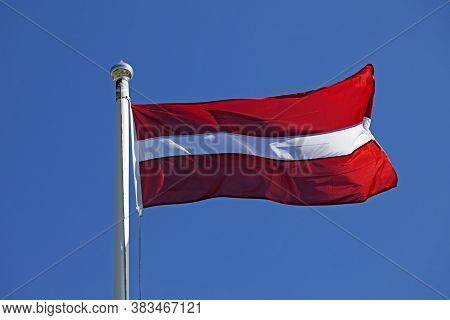 Latvian Flag Waving In The Wind On A Blue Summer Sky