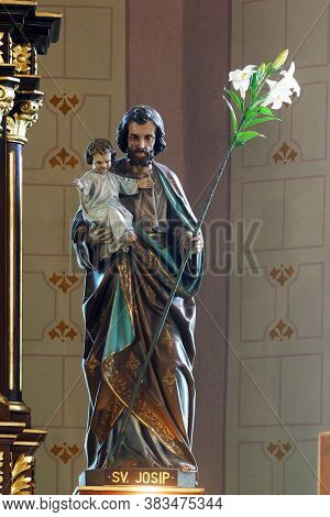 VELIKA GORICA, CROATIA - SEPTEMBER 28, 2012: St. Joseph holds the baby Jesus statue on the main altar in the Church of the Annunciation of the Blessed Virgin Mary in Velika Gorica, Croatia