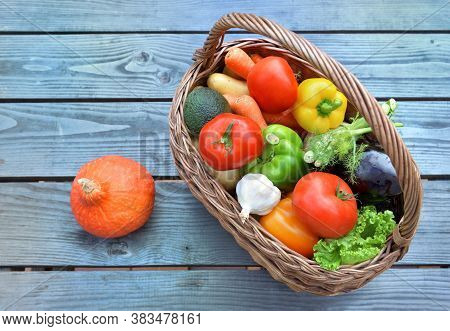 Various And Colorful Vegetables In A Wicker Basket Put On A Wooden  Table Next