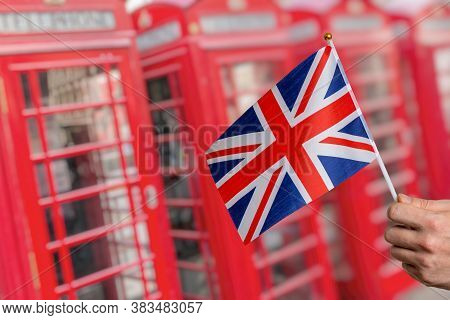 Flag Of Great Britain And Many London Red Phone Booths In Background.