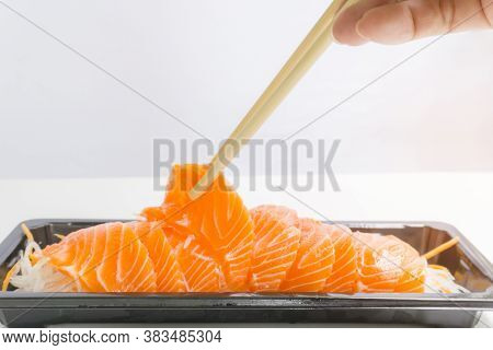 A Row Of Salmon Sashimi On Vegetable Sliced In Small Black Tray, A Bamboo Chopsticks In A Hand Clamp