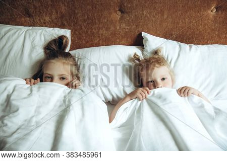 Two Children Hiding Under Duvet In Bed. Sisters Play, Indulge In The Bedroom In The Morning. Childre