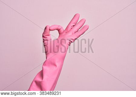 Hand of caucasian young man with cleaning glove over isolated pink background gesturing approval expression doing okay symbol with fingers
