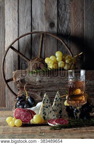 Rustic Still Life With Wine And Snacks. On An Old Wooden Table Wine, Blue Cheese, Dry-cured Sausage,