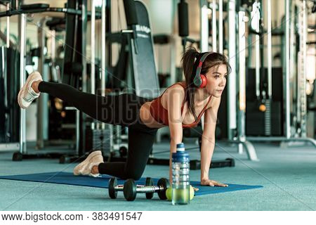 Full-length Of Young Beautiful Woman In Sportswear Doing Plank At Gym. Women And Ear Phone Listen Mu