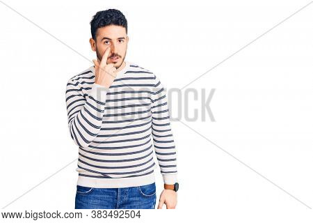 Young hispanic man wearing casual clothes pointing to the eye watching you gesture, suspicious expression