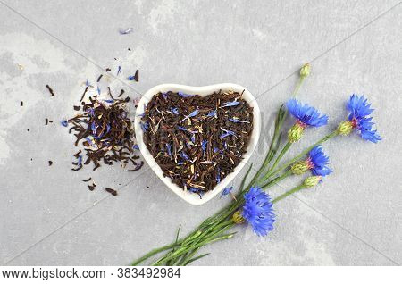 Blend Of Black Tea, Cornflowers Petals And Thyme In Ceramic Bowl With Fresh Blue Cornflowers