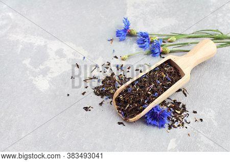 Black Tea With Flower Petals Of Cornflower And Thyme Herb In Wooden Scoop, Fresh Cornflowers.