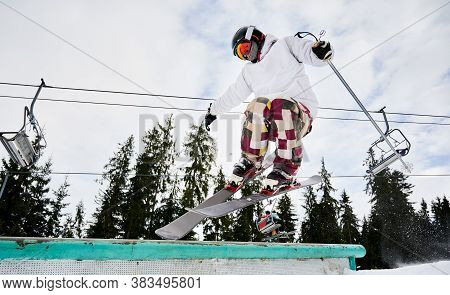 Male Skier In Ski Jacket And Helmet Making Jump On Winter Day. Man Freerider Jumping In The Air At S