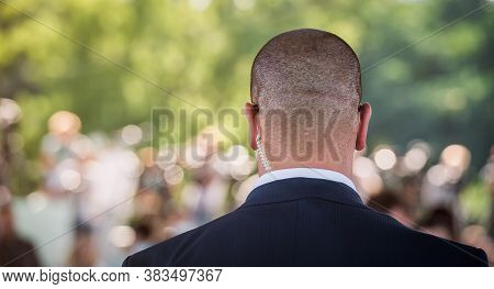 Security Guard Standing In The Business Meeting. Mature Security Guard Listening To Earpiece Against