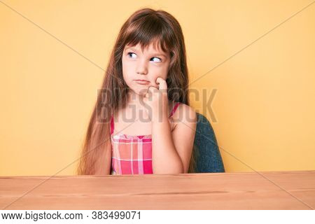 Little caucasian kid girl with long hair wearing casual clothes sitting on the table thinking concentrated about doubt with finger on chin and looking up wondering