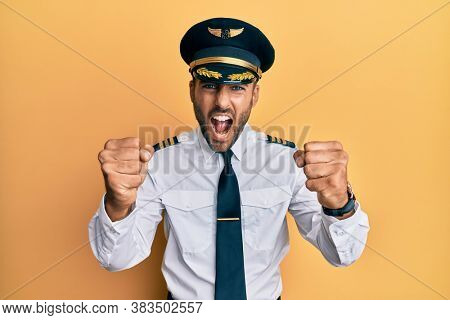 Handsome hispanic man wearing airplane pilot uniform angry and mad raising fists frustrated and furious while shouting with anger. rage and aggressive concept.