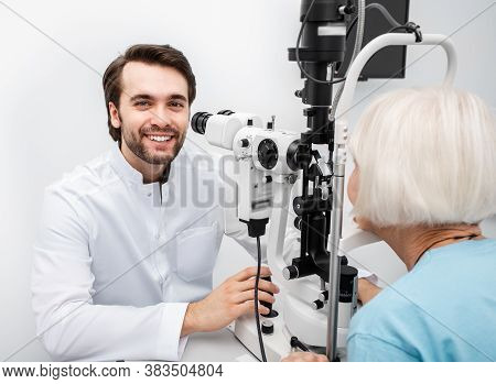 Portrait Of A Positive Ophthalmologist At Work. Ophthalmologist Checking Eyesight Of An Elderly Pati
