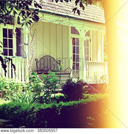Vintage Photo Of Iron Wrought Bench On The Veranda Of A Traditional Colonial Villa Facing A Garden O