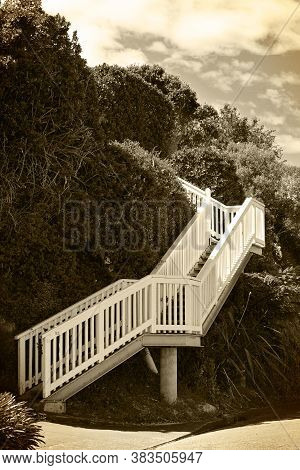 Vintage Black And White Photo Of White-railed Steep Stairway Leading Up The Hill On A Fine Day. Sepi