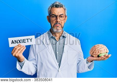 Middle age grey-haired man wearing doctor coat holding brain and anxiety message depressed and worry for distress, crying angry and afraid. sad expression.