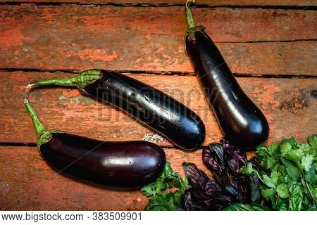 Eggplants And Herbs Lie On A Wooden Surface. Concept Of Biological, Bio Products, Bio Ecology, Grown