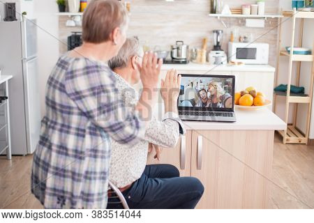 Happy Senior Woman Waving During A Video Conference With Family Using Laptop In Kitchen. Online Call