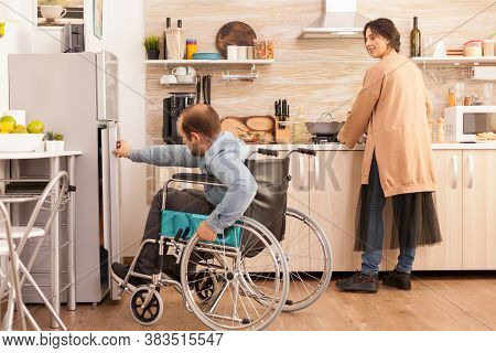 Woman In Kitchen Looking At Husband With Walking Disability Trying To Open Refrigerator Door. Disabl