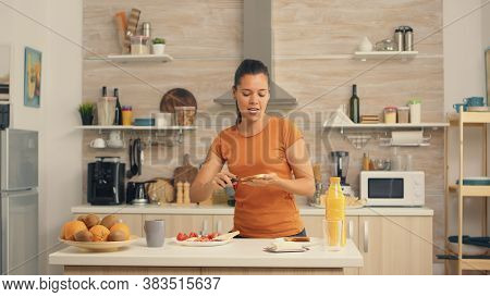Cheerful Woman In The Morning Dancing And Spreading Butter On Roasted Bread. Knife Smearing Soft But