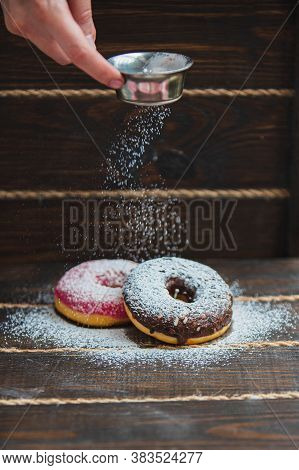 Donuts Sprinkled With Powdered Sugar On Wooden Table On Black Background. Food Background