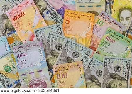 American Dollar Bills Notes Over Venezuelan Bolivar Banknote With Different Currency Paper Bills.