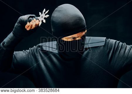 Ninja With A Sword And Shuriken Ready To Stab Enemy Over Black Background. Japanese Fighter Concept