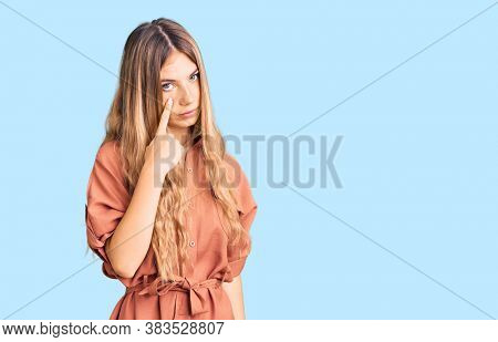 Beautiful caucasian woman with blonde hair wearing summer jumpsuit pointing to the eye watching you gesture, suspicious expression