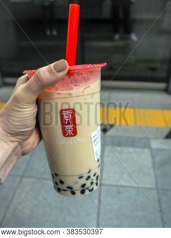 March 2019 - South Korea: Caucasian Female Hand Holding A Jumbo Size Black Milk Tea With Pearls Or B