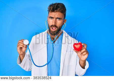 Young hispanic man wearing doctor uniform holding stethoscope and heart in shock face, looking skeptical and sarcastic, surprised with open mouth